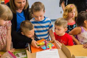 Children opening a box of school supplies